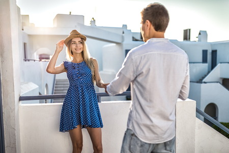 Summer at sunset, guy or man flirts with girl holding her hand. First date, romantic meeting