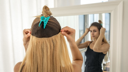 Instant hair extensions on hairpins for volume and elongation. Light blonde strands 写真素材