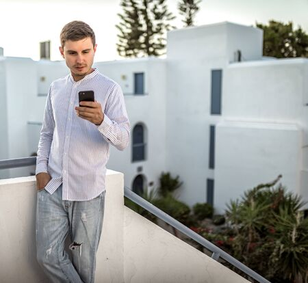 young man looks at the a smartphone, summer outside, place for text, phone outdoor