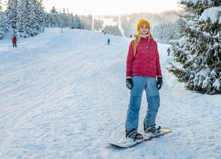young girl snowboarding, winter sport activity, red ski jacket and yellow a hat