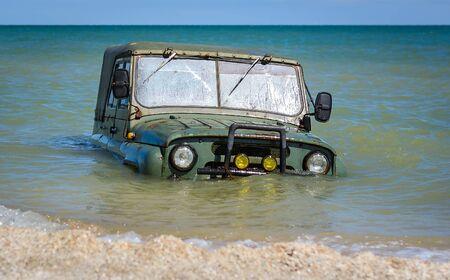 car stuck mud or submerged in sea water on beach ocean or sea