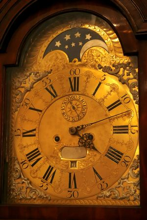 beat the clock: Ancient floor watch count modern time carved arrows showing on a gold dial transitoriness of life