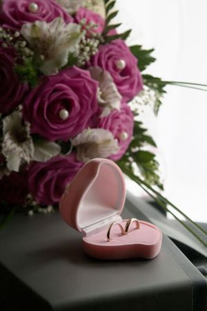 Wedding rings in a pink box of the form of near to a bouquet of the bride photo