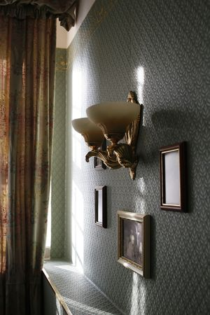 architectural studies: a lamp and frame with photos in an ancient interior in morning light