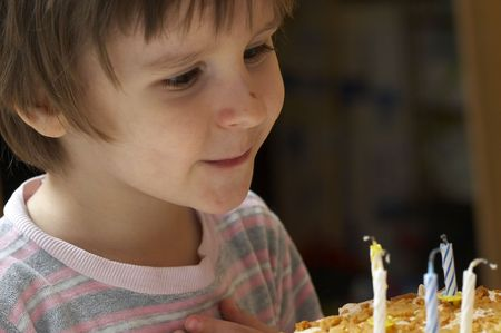 The boy blow out celebratory candles on name day pie and thinks of desire Stock Photo - 2471315