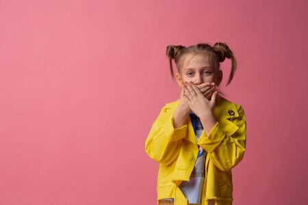 girl shut her mouth with her hands in yellow clothes on pink background. concept of silence 版權商用圖片