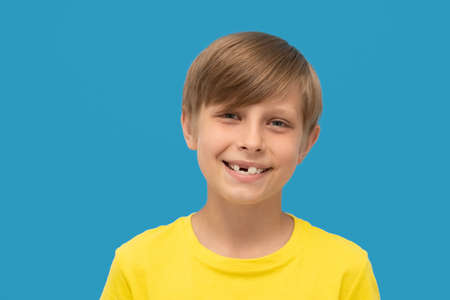 close up photo blond boy in yellow t-shirt shows a smile without front tooth.
