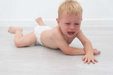 baby blonde boy crying lying on the field.