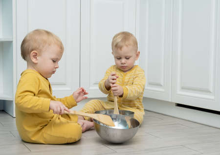 Twin boys play in the kitchen with kitchenware. Stock Photo