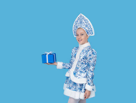 cute young girl wearing blue suit of snow maiden holding gift box. Isolated on blu background.