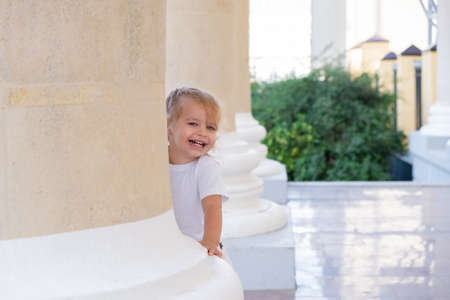 little blonde girl looks out from behind a pillar.