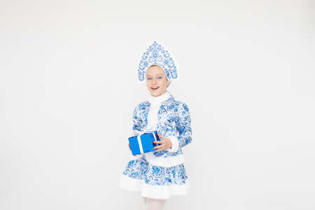 Attractive cute young girl wearing blue suit of snow maiden holding gift box on white background.
