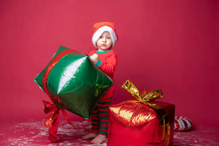 Toddler boy in Santa hat with Xmas gifts and candy cane on a red background.
