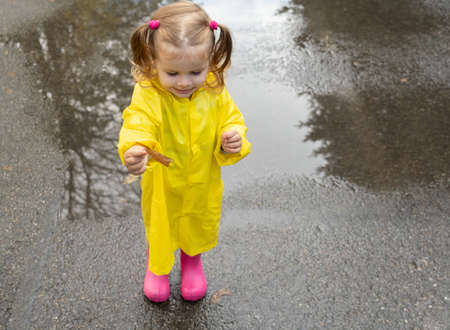 Cute baby girl toddler wearing yellow stylish raincoat pink rubber boots standing in a puddle.