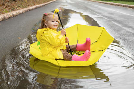 Cute baby girl wearing yellow stylish raincoat pink rubber boots sitting in umbrella in a puddle.