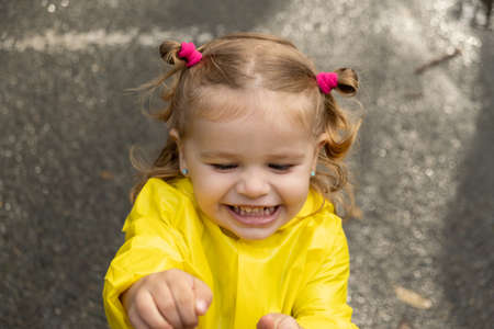 Cute blonde baby girl toddler wearing yellow stylish raincoat closeup. childhood. 版權商用圖片
