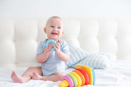funny baby boy sits on bed and play with a toy childrens pyramid.