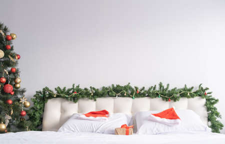 light bedroom with Christmas decorations. white bedding with Santa hats. copy space. 版權商用圖片