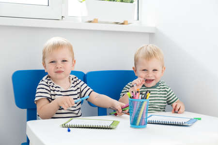 Education and hobby. two blonde twins boys paint with felt pen. Stok Fotoğraf