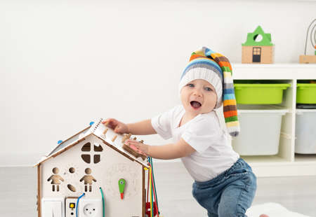 baby toddler boy playing with busy board at home. Developing games for children.