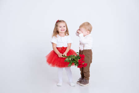 shy little boy giving bouquet of roses to toddler girl on valentines day on white background Standard-Bild