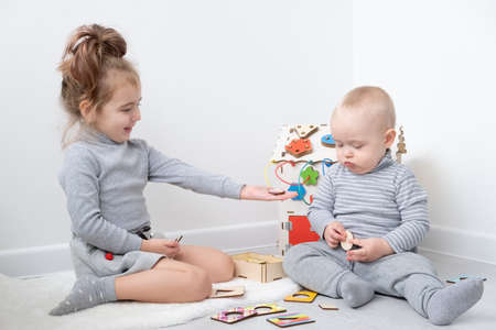 baby boy playing with older sister with wooden toys. early children development 版權商用圖片