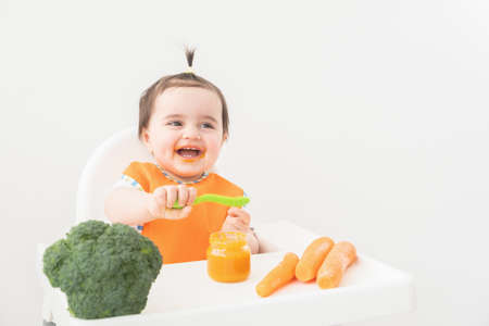 Baby girl in orange bib sitting in a Childs chair eating vegetable puree on white background