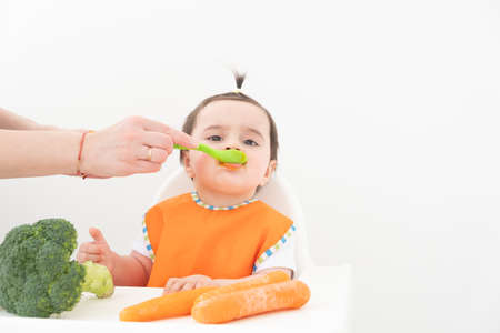 Baby girl sitting in a Childs chair eating vegetable puree on white background. Mom feeds baby