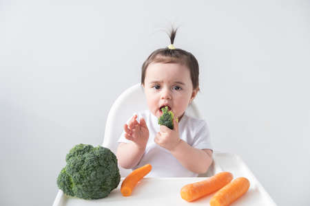 Baby girl sitting in baby chair eating carrot and broccoli on white background Banque d'images