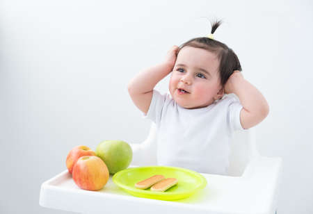 baby girl in baby chair eating apples and cookies on white background. Baby first solid food Banque d'images