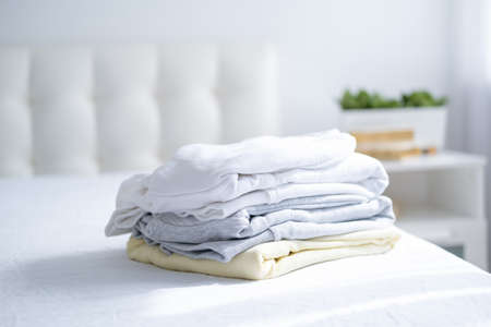 stack of women colorful sweatshirts, hoodies in pastel colors on white bed. Seasonal shopping, laundry, vacation concept.