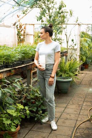 attractive women gardener in casual clothes holding plastic pots in greenhouse Stock fotó