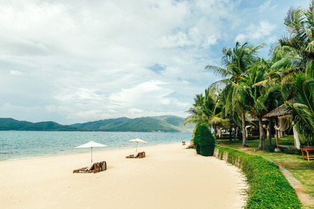 hon: white sand beach resort with sunbeds and white umbrellas with palma trees and mountains background Stock Photo