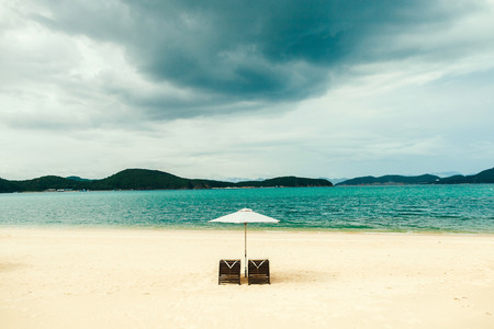 white sand beach resort with two sunbeds and umbrella with nobody and rainy sky