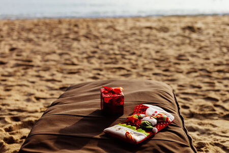 red box: Christmas and new year holidays on the beach. Christmas stocking and gift red box on sunbed with sea view and nobody