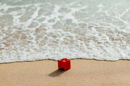 red box: present gift in red box  on the beach in tropics. Present red box flowing in the sea. christmas holideys on the beach