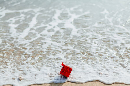red box: present gift in red box  on the beach in tropics. Present red box flowing in the sea