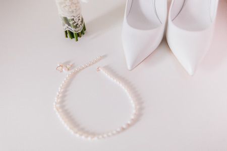 wedding pearl earrings and necklace close up with wedding shoes and bouquet background photo