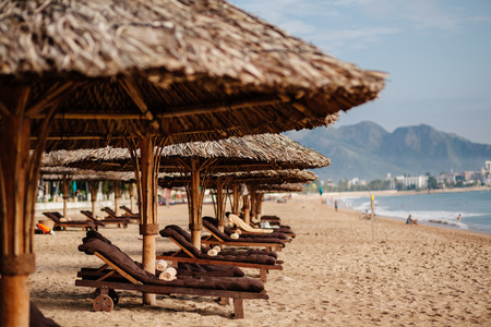 sunbeds: luxury beach resort with wooden sunbeds and umbrellas with nobody  in Asia, Vietnam beach, Nha Trang