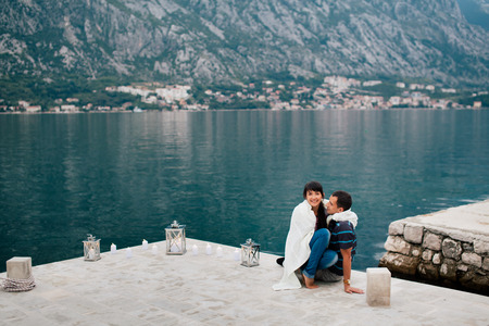 couple on the beach with candkes in romantic place with mountain and bay view in Montenegro photo
