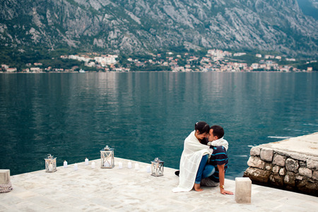 couple on the beach with candkes in romantic place with mountain and bay view in Montenegro