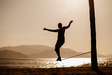 slack: man balancing on slackline with sea view silhouette Stock Photo