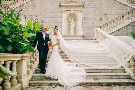church: bride with long veil and groom at stairway Stock Photo