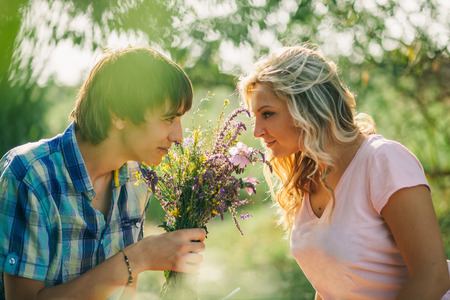 love and friendship: teenage couple dating on picnic in green park with flowers eye to eye look