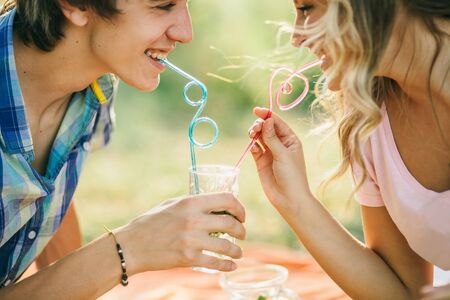 teenage couple drink cocktail from one glass and smiling photo