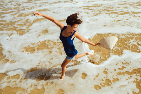 non la: happy girl with vietnamese hat jumping on the beach  top view