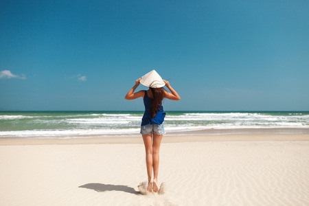 non la: happy girl in vietnamese hat jumping on the beach  with sea view in Asia Stock Photo