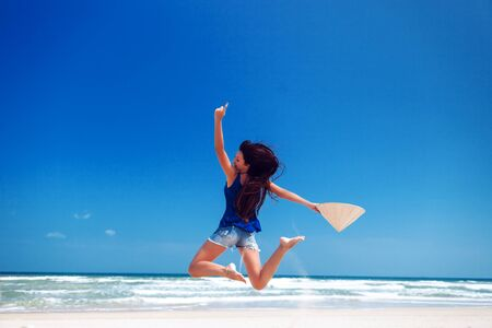 non la: happy girl in vietnamese hat jumping on the beach  with sea view Stock Photo