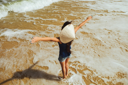 non la: happy girl in vietnamese hat jumping with hands up on the beach  top view