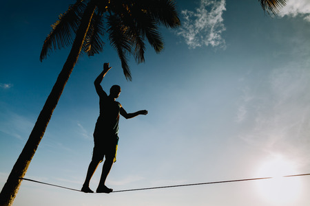 teenage balancing on slackline with sky view on the beach silhouette Stock Photo